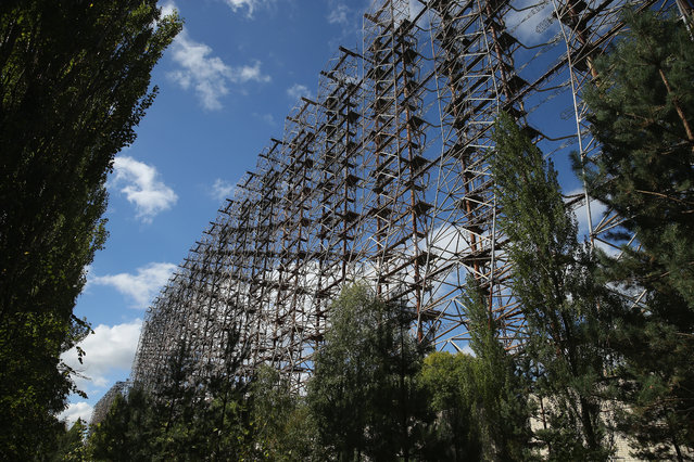 "An abandoned Soviet Cold War-era radar system known as ""The Woodpecker"" used to detect incoming missiles and that measures 140 meters tall stands inside the Chernobyl Exclusion Zone on September 30, 2015 near Chornobyl, Ukraine. The Chernobyl Exclusion Zone is a 2,600 square kilometer restricted access zone established in the contaminated area around the Chernobyl nuclear power plant. (Photo by Sean Gallup/Getty Images)"