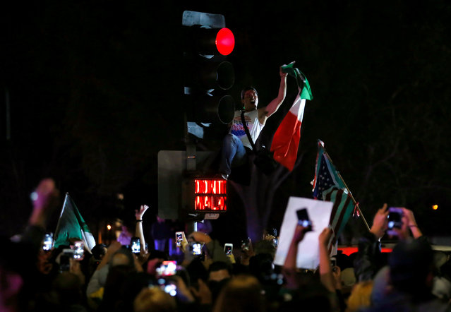 A demonstrator climbs a traffic light outside Republican U.S. presidential candidate Donald Trump's campaign rally in Costa Mesa, California, April 28, 2016. (Photo by Mike Blake/Reuters)