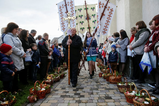 "Believers prepare ""paskha"" cakes, eggs and other food to be consecrated at the Greek-Catholic church ahead of midnight Easter mass in Pustomyty village near Lviv, Ukraine, April 30, 2016. (Photo by Gleb Garanich/Reuters)"