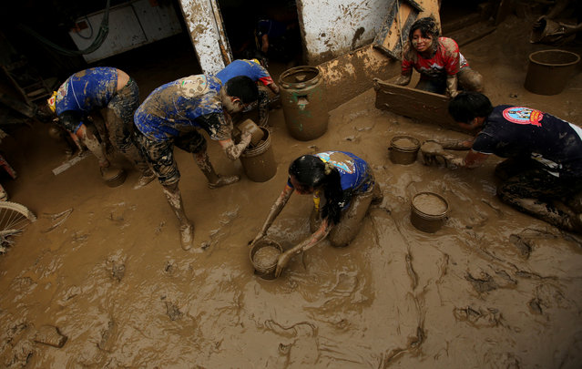 Volunteers clean a flooded home, after rivers breached their banks due to torrential rains, causing flooding and widespread destruction in Cajamarquilla, Lima on March 19, 2017. (Photo by Mariana Bazo/Reuters)