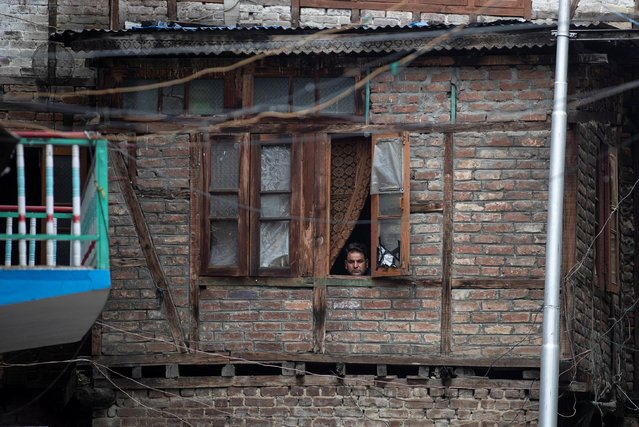 A Kashmiri man looks out of his house during restrictions after the scrapping of the special constitutional status for Kashmir by the government, in Srinagar, August 14, 2019. (Photo by Danish Siddiqui/Reuters)