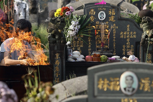 A woman visit the tomb of her loved ones to pay respect and burn offerings at the Choa Chu Kang Chinese Cemetery during the Qing Ming Festival on April 4, 2013 in Singapore. (Photo by Suhaimi Abdullah/Getty Images)