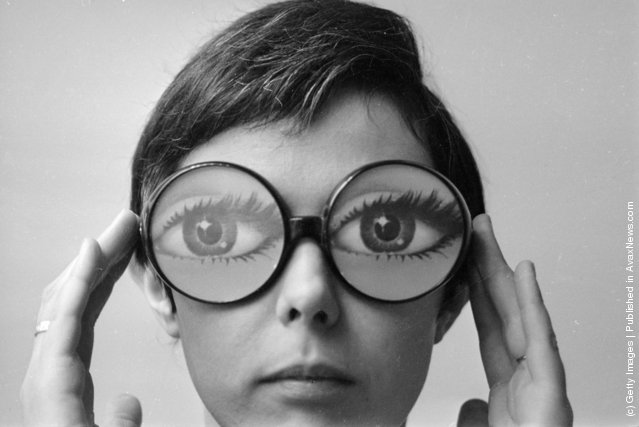 1969: Big round glasses magnify the eyes of the model wearing fashion glasses designed by Marly, a Paris optician