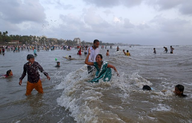 People play on a beach along the Arabian Sea on a hot summer day in Mumbai, India, July 5, 2015. (Photo by Danish Siddiqui/Reuters)