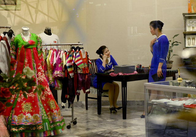 What appears to be girl talk between attendants at a gift shop for foreigners at the Yanggakdo Hotel in Pyongyang, North Korea on May 6, 2016. (Photo by Linda Davidson/The Washington Post)