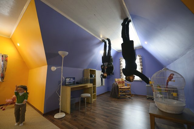 "A picture rotated 180 degrees shows visitors walking inside an ""upside-down house"" attraction at the VVTs the All-Russia Exhibition Center in Moscow, on January 14, 2014. The attraction to experience a new perspective of a house standing upside down was opened first time in Russia, the show organisers said. (Photo by Alexander Nemenov/AFP Photo)"