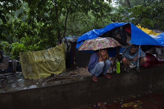 Indian men take shelter during monsoon rains in New Delhi, India, Saturday, July 11, 2015. (Photo by Bernat Armangue/AP Photo)