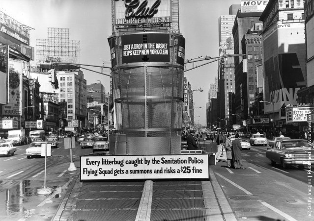 1964:  A gigantic litter basket in Times Square, New York with a sign saying, 'Just a Drop in the basket keeps new York Clean'