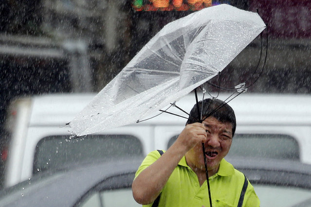 A Taiwanese man holds an umbrella against powerful gusts of wind generated by typhoon Lekima in Taipei, Taiwan, Friday, August 9, 2019. (Photo by Chiang Ying-ying/AP Photo)