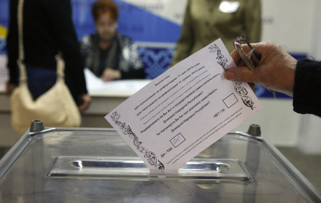 A voter casts a ballot during a referendum on the status of the Donetsk region in the eastern Ukrainian city of Slaviansk May 11, 2014. Ukrainian leader Oleksander Turchinov warned pro-Russian eastern regions they would be stepping into the abyss if they voted for self-rule on Sunday in a referendum that has raised Western fears of a slide to full civil war. (Photo by Baz Ratner/Reuters)