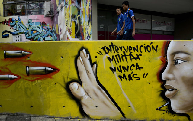 """Schoolboys walk next to a graffiti reading """"Military intervention never more"""" at the 13 Commune shantytown in Medellin, Antioquia department, Colombia on July 15, 2015. In 2002, Medellin was rocked by violence after the government's decision to recover part of the city disputed by right-wing paramilitaries and militias, during which, dozens of people were killed, more than 100 people were injured, 98 went missing and 200 families were displaced. (Photo by Raul Arboleda/AFP Photo)"""