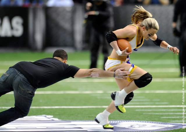 A fan tries to tackle league MVP Kyle DeHaven #1 of the Baltimore Charm during a halftime promotion at the Lingerie Football League's Lingerie Bowl IX between the Los Angeles Temptation and the Philadelphia Passion at the Orleans Arena