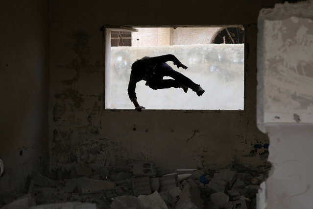 Parkour coach Ibrahim al-Kadiri, 19, demonstrates his parkour skills amid damage in the rebel-held city of Inkhil, west of Deraa, Syria, February 4, 2017. Led by Ibrahim, the team trains on quiet days. (Photo by Alaa Al-Faqir/Reuters)