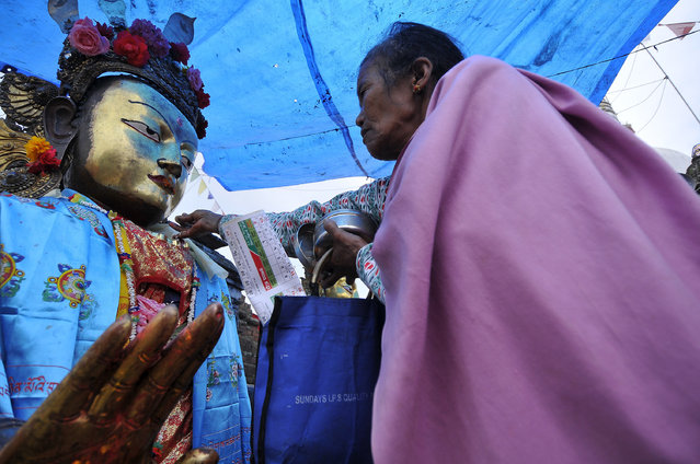 Nepalese Devotee offering ritual prayer towards Dipankar Buddha puts at the premises of Chiloncho Stupa during celebration the 2,561 Buddha Purnima festival, Birth Anniversary of Lord Gautam Buddha at Chiloncho, Kirtipur, Kathmandu on Wednesday, May 10, 2017. Buddhists around the world, Cambodia; Thailand; Myanmar; Bhutan; Sri Lanka; Laos; Mongolia; Japan; Singapore; Taiwan including Nepal, observe Buddha Purnima festival which falls on the same day of full moon of the month calendar. The occasion offerings of flower, incense and candles, an exchange of gifts as blessings, prayers, sermons and group meditations. (Photo by Narayan Maharjan/NurPhoto via Getty Images)