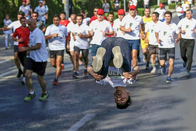 An Iraqi Kurdish man performs a backflip as runners take part in the 8th International Arbil Marathon in Arbil, the capital of the northern Iraqi Kurdish autonomous region, on October 25, 2018. (Photo by Safin Hamed/AFP Photo)
