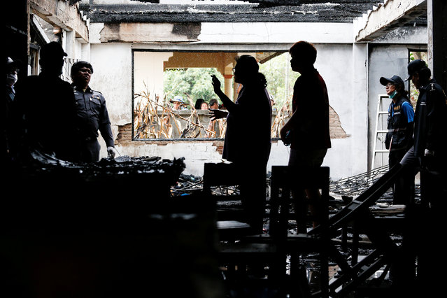 Forensic experts inspect a burnt building at the Pitakkiat Wittaya School in the northern province of Chiang Rai, Thailand, May 23, 2016. (Photo by Athit Perawongmetha/Reuters)