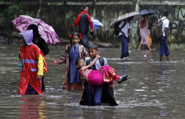 An Indian boy carries his sister and wades through a waterlogged street on his way to school as it rains in Mumbai, Maharashtra state, India, Tuesday, July 21, 2015. (Photo by Rajanish Kakade/AP Photo)
