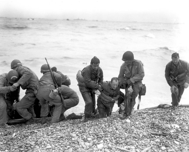 Members of an American landing party assist troops whose landing craft was sunk by enemy fire off Omaha beach, near Colleville sur Mer, France, June 6, 1944. REUTERS/Weintraub/US National Archives