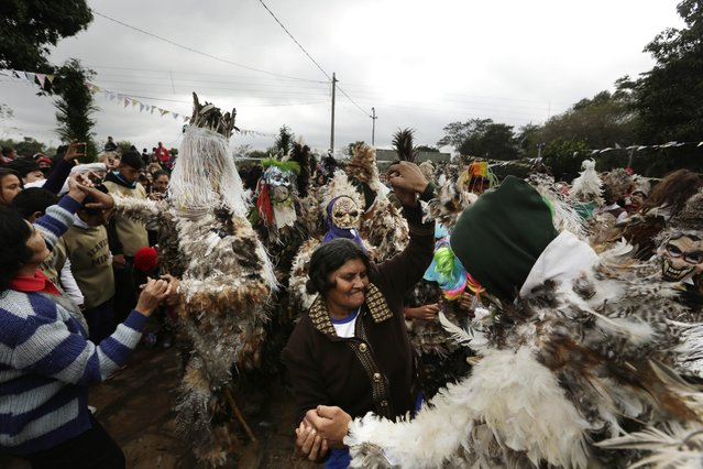 Revelers dance during the feast day celebrations honoring St. Francisco Solano, in Emboscada, Paraguay, Friday, July 24, 2015. Paraguayan Catholics honored the Spanish friar, also known as St. Francisco Solanus, in a a mix of Indian and Catholic beliefs Friday. The festival begins with a Mass, continues with a procession of the diminutive statue of the saint, and ends with pledges covered in feathers from head to toe, dancing with fellow parishioners. (Photo by Jorge Saenz/AP Photo)