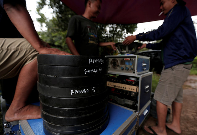 """Workers stand next to cans containing copies of the film """"Rambo"""", before a wedding party in Bogor, Indonesia, February 18, 2017. Indonesian entrepreneur Kamaluddin loves the gritty look of old 35-millimeter film so much that he spends most of his nights screening vintage movies at weddings and parties around Jakarta, the capital. Filmmakers and cinemas have almost completely phased out the 35-mm. format in the past decade as they switch to cheaper, better quality digital formats. But for Kamaluddin, running a 'mobile cinema' means bringing nostalgia and entertainment to the city's poorer residents. """"It's more artistic and the sound is much better than digital"""", he said. """"If you watch three movies in a row, you won't feel tired, just relaxed"""". He transports a 35-mm projector and sound system, films, a screen and large tent in his truck. At the venue, usually an open field or outside the home of a customer holding a party or celebration, people gather to watch as Kamaluddin sets up his equipment. The movies usually run into the early hours of the morning, with street vendors selling food, clothes and toys often setting up nearby, to sell their wares to the cinema-goers. Viewers get a chance to reacquaint themselves with films from Hollywood's golden era and movies from India's Bollywood, long out of circulation. Bollywood movies are hugely popular in Indonesia, especially on its islands of Bali and Java, where music and dance are heavily influenced by Indian tradition and performing arts. """"This theater is free of charge and we can watch old movies which we hardly find out there"""", said one viewer, Nurul Fitriyah, as she watched an old film on a huge fabric screen. But earnings have fallen steadily in the mobile cinema business as the younger middle class flocks to air-conditioned movie theaters that offer reclining chairs, or even beds, alongside fast food and soft drinks. """"In 1997, in one night I could set up four screens in four different locations"""", said Kamaluddin,"""