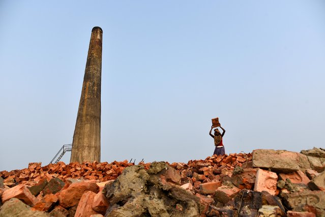 A labourer carries bricks in a kiln at Langolpota village in North 24 Parganas district in the eastern state of West Bengal, India, November 26, 2019. (Photo by Ranita Roy/Reuters)