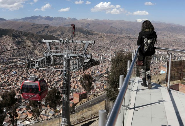 A woman looks at La Paz city from the Jacha Qhatu cable car station in El Alto, July 23, 2015. (Photo by David Mercado/Reuters)