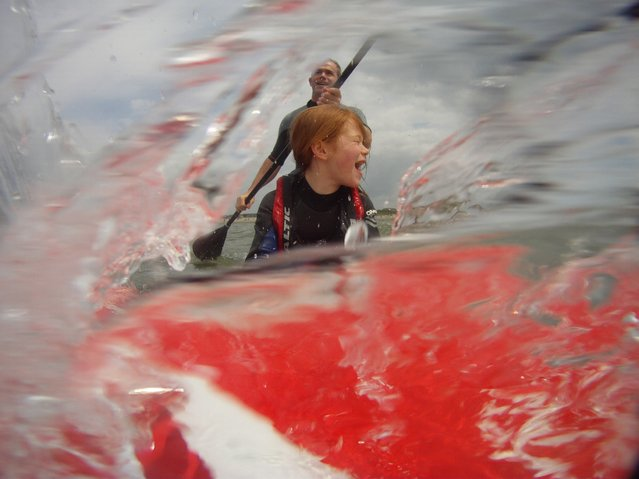 """""""Faster Daddy"""". Catching the waves on a paddle board with my daughter. Photo location: West Wittering Beach, West Sussex, UK. (Photo and caption by Jason Wilkins/National Geographic Photo Contest)"""