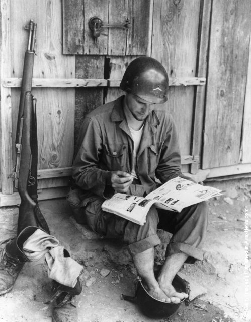An American soldier relaxes by taking a footbath in a spare helmet whilst reading a magazine, during the Korean War, 1950