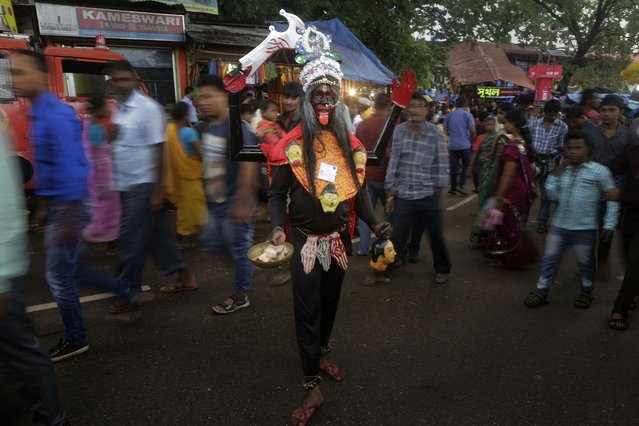 An Indian man stands dressed like Hindu goddess Kali to attract alms from devotees during the Ambubasi festival at the Kamakhya Hindu temple in Gauhati, India, Sunday, June 22, 2014. The annual festival where hundreds of holy men from an esoteric form of Hinduism, gather to perform rituals at the temple begins on June 22. (Photo by Anupam Nath/AP Photo)