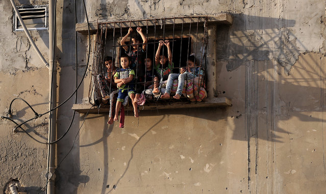 A picture made available on 06 May 2016 shows Palestinian children sitting at the window of their family house in the east of Al Shejaeiya neighborhood, east of Gaza City near the border between the Gaza strip and Israel, 05 May 2016. Israeli air strikes hit four Hamas sites in the east of Gaza City overnight. According to media reports, the airstrikes were conducted as retaliation for mortar attacks on Israeli Defense Force personnel along the border region. (Photo by Mohammed Saber/EPA)