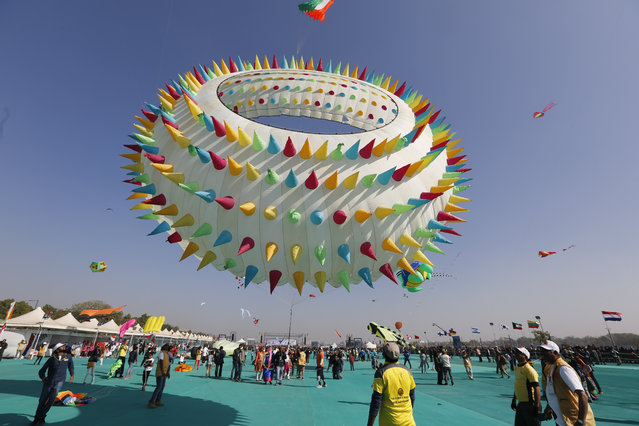 Indians watch a huge kite fly during International kite festival in Ahmadabad, India, Sunday, January 6, 2019. Kite flyers from various countries and across India are participating in the festival that is annually held on the Sabarmati riverfront here. (Photo by Ajit Solanki/AP Photo)