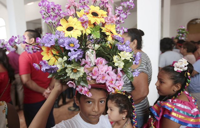 A child carries a figurine of Santo Domingo de Guzman on his head during celebrations honoring the patron saint, in Managua, Nicaragua July 31, 2015. (Photo by Oswaldo Rivas/Reuters)