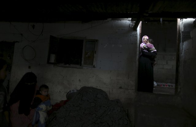 A Palestinian woman carries her daughter at her house during a power cut in the northern Gaza Strip March 25, 2015. (Photo by Mohammed Salem/Reuters)