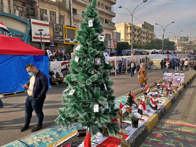 People pass by a Christmas tree with portraits of anti-government protesters who killed under fire from security forces in Tahrir Square during ongoing protests in Baghdad, Iraq, Thursday, December 12, 2019. (Photo by Khalid Mohammed/AP Photo)