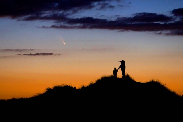 Father and Son Observe Comet PanSTARRS by Chris Cook (USA). A father and his young son watch the evening display of Comet PanSTARRS on First Encounter Beach, Eastham, Massachusetts, USA. The photographer had spent weeks preparing the shoot to capture the comet, which will not be seen again for over 100,000 years, in order to foster his son's interest in astronomy. (Photo by Chris Cook)