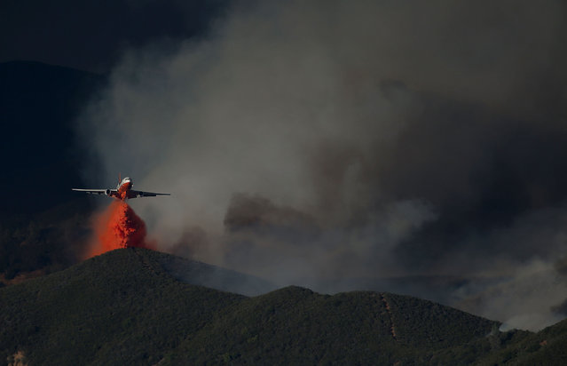A DC-10 firefighting aircraft drops fire retardant on a ridge in front of the Rocky Fire on August 3, 2015 near Clearlake, California. Nearly 3,000 firefighters are battling the Rocky Fire that has burned over 60,000 acres has forced the evacuation of 12,000 residents in Lake County. The fire is currently 12 percent contained and has destroyed at least 14 homes. 6,300 homes are threatened by the fast moving  blaze. (Photo by Justin Sullivan/Getty Images)