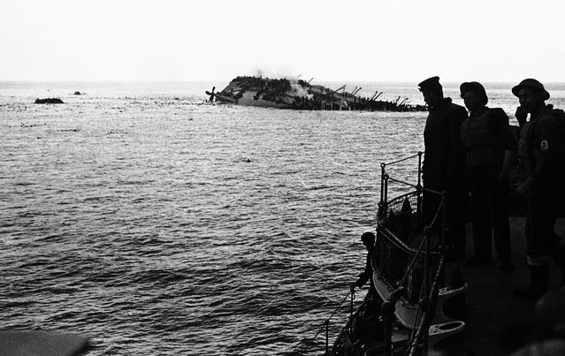 The dramatic scene as the Cunard White Star liner Lancastria was sunk on August 3, 1940. The Lancastria was evacuating British nationals and troops from France, and had boarded as many as possible for the short trip – an estimated 4,000 to 9,000 passengers were aboard. A German Junkers 88 aircraft bombed the ship shortly after it departed, and it sank within twenty minutes. While 2,477 were rescued, an estimated 4,000 others perished by bomb blasts, strafing, drowning, or choking in oil-fouled water. Photo taken from one of the rescue boats as the liner heels over, as men swarm down her sides and swim for safety to the rescue ships. Note the large number of bobbing heads in the water