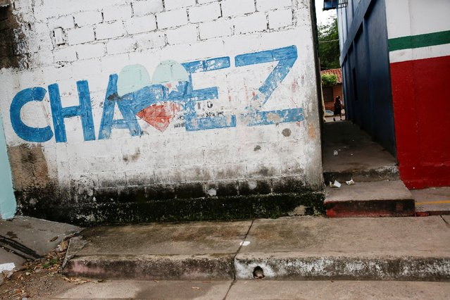 A girl walks past a mural that refers to Venezuela's late President Hugo Chavez as she arrives to an improvised classroom above a state-run supermarket, which is part of state school Monsenor Marco Tulio Ramirez Roa, in La Fria, Venezuela, June 2, 2016. (Photo by Carlos Garcia Rawlins/Reuters)
