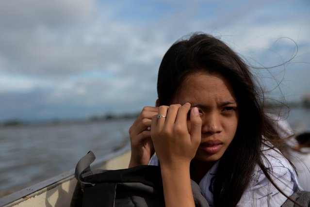 Danica Martinez, 16, shields her face away from the sun as she travels home from school by boat in Bulakan, Bulacan, north of Manila, Philippines, November 25, 2019. (Photo by Eloisa Lopez/Reuters)