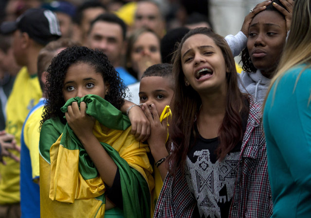 Brazil soccer fans watch their team lose to Germany at a World Cup semifinal game on TV in Sao Paulo, Brazil, Tuesday, July 8, 2014. (Photo by Rodrigo Abd/AP Photo)