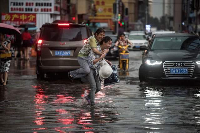A woman holds an elderly woman on her back to cross a flooded street after a heavy rain in Shenyang, Liaoning province on July 14, 2017. (Photo by Fred Dufour/AFP Photo)