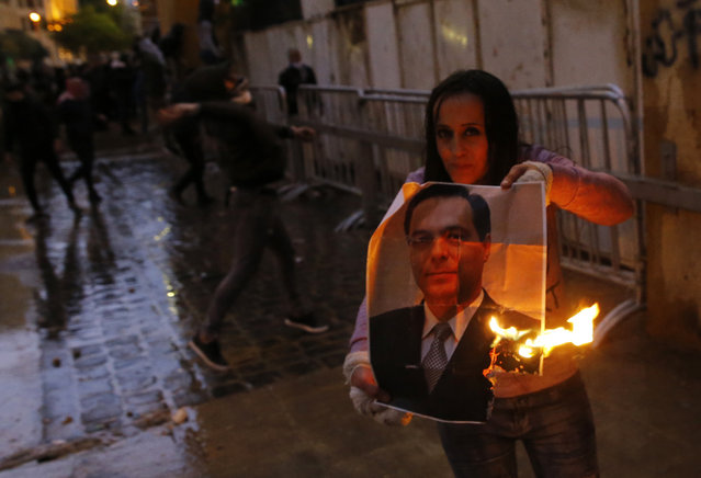 An anti-government protester burns a picture of new Lebanese Prime Minister Hassan Diab during ongoing protests in Beirut, Lebanon, Wednesday, January 22, 2020. Lebanon's new government held its first meeting Wednesday, a day after it was formed following a three-month political vacuum, with the prime minister saying his Cabinet will adopt financial and economic methods different than those of previous governments.  (Photo by Bilal Hussein/AP Photo)