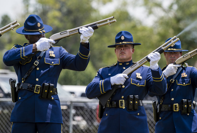 Louisiana State Police Officers fire weapons during a salute for Shreveport Police Officer Thomas LaValley during his burial service in the cemetery at Holy Rosary Catholic Church, Monday, August 10, 2015, in St. Amant, La. LaValley was killed Wednesday, Aug. 5 while answering a call about a suspicious person at a home. (Photo by Paul Kieu/The Daily Advertiser via AP Photo)