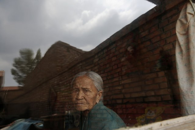 """Former Chinese """"comfort woman"""" Zhang Xiantu looks through the window of her house in Xiyan Town, Shanxi Province, China, July 18, 2015. (Photo by Kim Kyung-Hoon/Reuters)"""