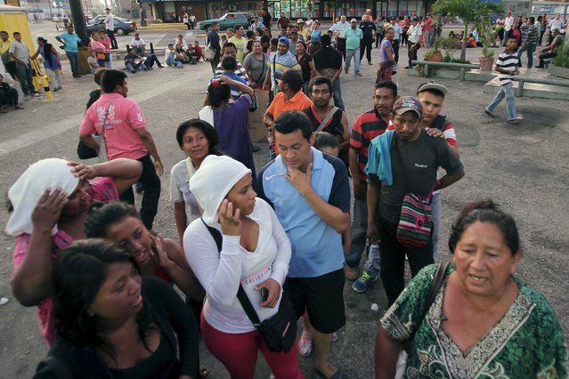 People queue while waiting for opening time to buy staple items, outside a supermarket in Maracaibo, Venezuela August 8, 2015. As dawn breaks over the scorching Venezuelan city of Maracaibo, young mothers and a handful of kids stir outside a supermarket where they spent the night, hoping to be first in line for scarce rice, milk – or whatever is available. (Photo by Isaac Urrutia/Reuters)