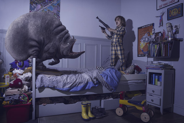 """Diego fights a monster with a """"gun"""" in his bedroom in Laure Fauvel's """"Terreurs"""", 2014, in Paris, France. An imaginative photographer has brought to life monsters that haunt children's nightmares. Armed with sticks, wands and swords the eight and nine year-olds appear to be getting the upper-hand against the villains. Parisian photographer Laure Fauvel, 22, said: I wanted the children not be victims and to fight the monsters. (Photo by Laure Fauvel/Barcroft Media)"""