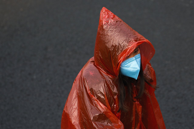 A masked woman in a plastic rain coat walks on a street in Beijing, Tuesday, February 11, 2020. China's daily death toll from a new virus topped 100 for the first time and pushed the total past 1,000 dead, authorities said Tuesday after leader Xi Jinping visited a health center to rally public morale amid little sign the contagion is abating. (Photo by Andy Wong/AP Photo)