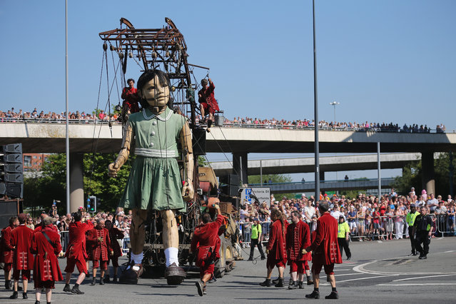 Crowds watch from a motorway bridge as The Little Giant Girl,walks through the streets of Liverpool on July 25, 2014 in Liverpool, England. French street theatre company Royal de Luxe are putting on a show throughout the city as part of Liverpool's World War I centenary commemorations from July 23-27. (Photo by Christopher Furlong/Getty Images)
