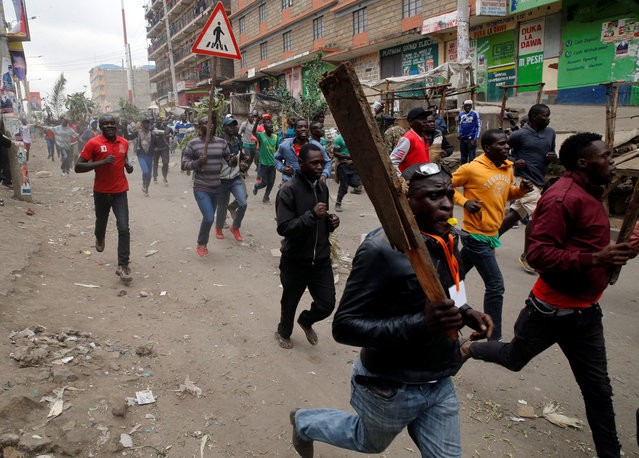 Demonstrators carry sticks as they run along a street in Mathare, Kenya August 9, 2017. (Photo by Thomas Mukoya/Reuters)