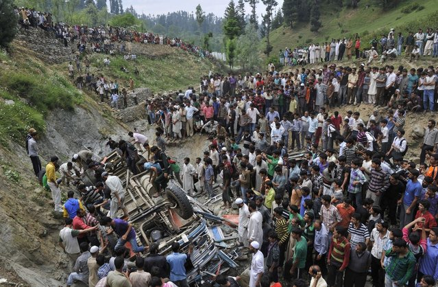 Kashmiri villagers stand near the wreckage of a bus at Nambal Nard some 55 kms northwest of Srinagar on July 11, 2012